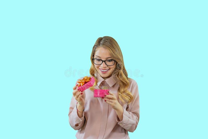 Πορτρέτο μιας νέας ξανθής γυναίκας που ανοίγει ένα χαμόγελο δώρων που εξετάζει ένα δώρο, νέες διακοπές έτους, γενέθλια, γάμος στοκ εικόνα με δικαίωμα ελεύθερης χρήσης