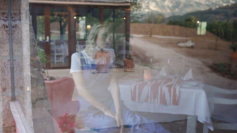 Πορτρέτο μιας νέας ξανθής συνεδρίασης γυναικών στην κουζίνα στο σπίτι r Νέα ελκυστική ξανθή συνεδρίαση στην κουζίνα στοκ φωτογραφία με δικαίωμα ελεύθερης χρήσης