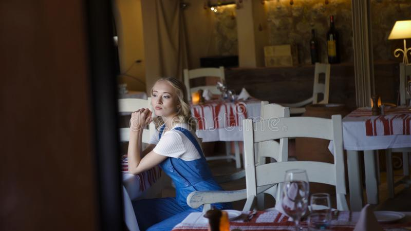 Πορτρέτο μιας νέας ξανθής συνεδρίασης γυναικών στην κουζίνα στο σπίτι r Νέα ελκυστική ξανθή συνεδρίαση στην κουζίνα στοκ φωτογραφία