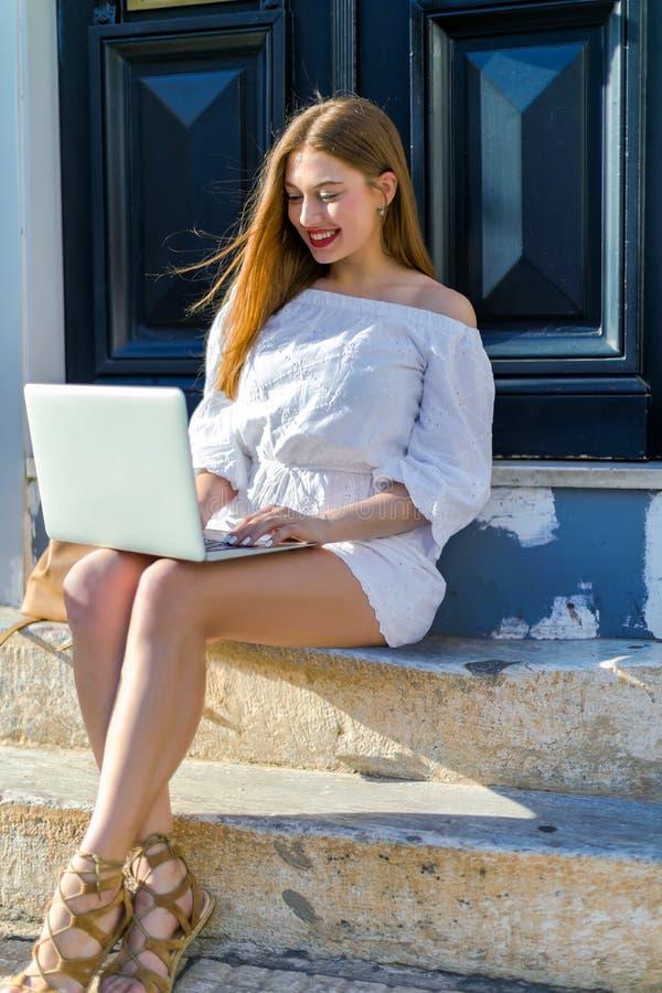 Πορτρέτο μιας νέας συνεδρίασης γυναικών στα σκαλοπάτια πόλεων και της χρησιμοποίησης ενός φορητού προσωπικού υπολογιστή στοκ εικόνες