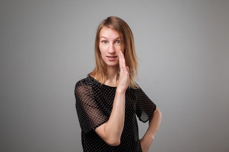 Πορτρέτο μιας νέας όμορφης γυναίκας που λέει τις μυστικές πληροφορίες, που κρατά το χέρι της κοντά στο στόμα στοκ εικόνες