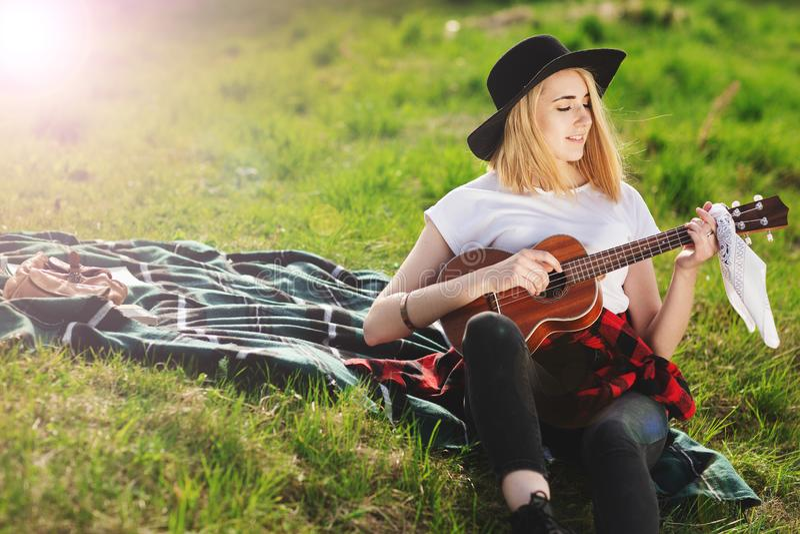 Πορτρέτο μιας νέας όμορφης γυναίκας σε ένα μαύρο καπέλο Συνεδρίαση κοριτσιών στη χλόη και την κιθάρα παιχνιδιού στοκ εικόνες