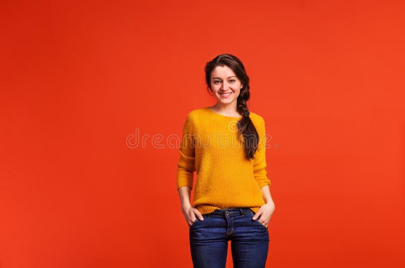 Πορτρέτο μιας νέας όμορφης γυναίκας στο στούντιο σε ένα κόκκινο υπόβαθρο στοκ φωτογραφίες με δικαίωμα ελεύθερης χρήσης