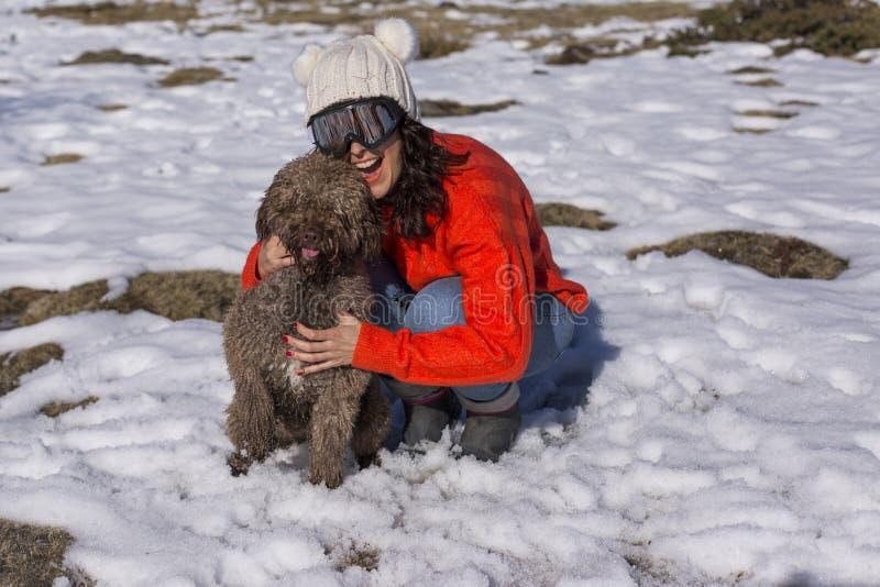 Πορτρέτο μιας νέας όμορφης γυναίκας στο χιόνι με το χαριτωμένο σκυλί της r Φθορά των θερμών ενδυμάτων lifestyle στοκ εικόνες