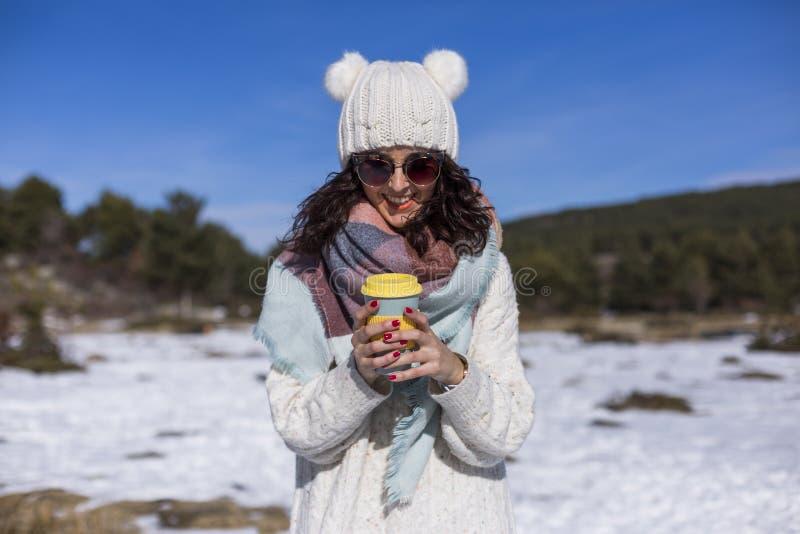 Πορτρέτο μιας νέας όμορφης γυναίκας στο χιόνι που κρατά ένα φλιτζάνι του καφέ ή ένα τσάι r Φθορά των θερμών ενδυμάτων lifestyle στοκ εικόνες