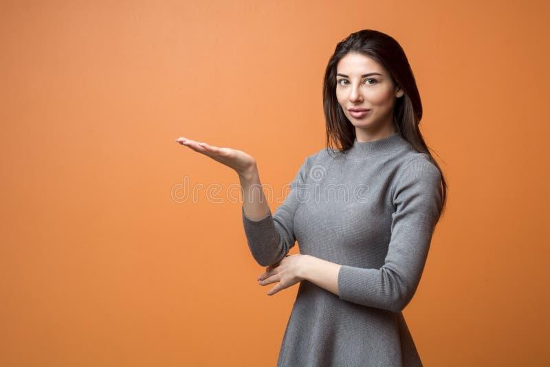 Πορτρέτο μιας νέας όμορφης επιχειρησιακής γυναίκας στο ουδέτερο φόρεμα που αντέχει το κενό χέρι και που εξετάζει τη κάμερα στοκ φωτογραφίες με δικαίωμα ελεύθερης χρήσης