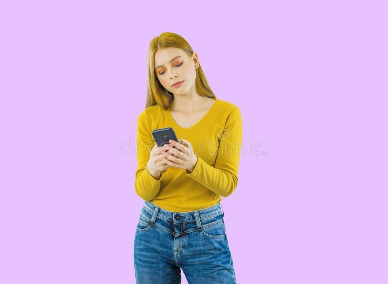 Πορτρέτο μιας νέας όμορφης κοκκινομάλλους γυναίκας που κρατά ένα smartphone στα χέρια της και δακτυλογραφώντας sms ή τις πληροφορ στοκ εικόνα με δικαίωμα ελεύθερης χρήσης