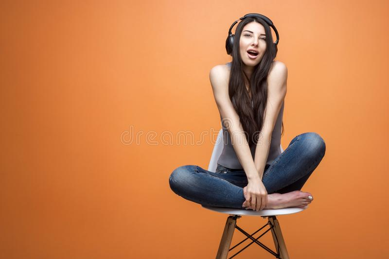 Πορτρέτο μιας νέας όμορφης συνεδρίασης κοριτσιών στην προεδρία και ακούοντας τη μουσική μέσω της κάσκας στο πορτοκαλί κλίμα στοκ φωτογραφίες με δικαίωμα ελεύθερης χρήσης