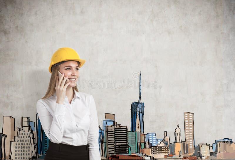 Πορτρέτο μιας ξανθής επιχειρηματία που φορά ένα κίτρινο σκληρό καπέλο και που μιλά στο smartphone της στοκ εικόνα