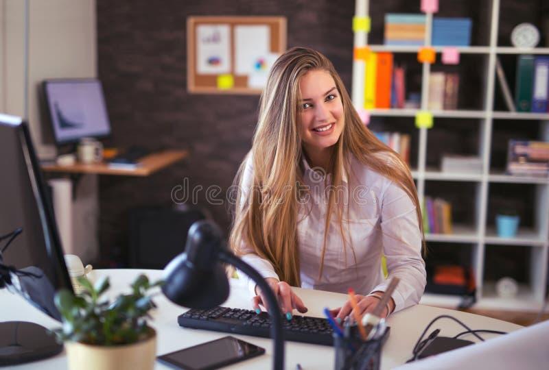 Πορτρέτο μιας ξανθής θηλυκής συνεδρίασης επιχειρησιακών γυναικών στο γραφείο της στοκ φωτογραφία