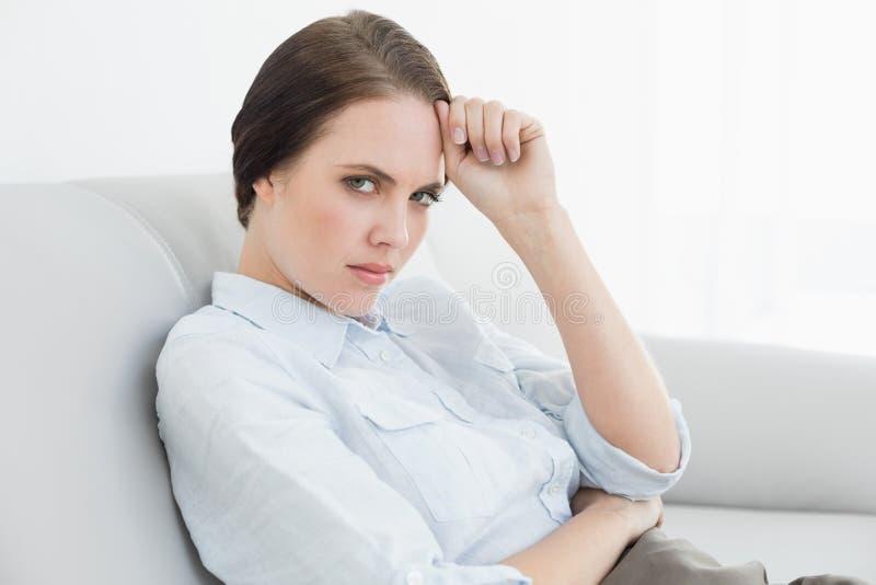 Πορτρέτο μιας σοβαρής καλά ντυμένης συνεδρίασης γυναικών στον καναπέ στοκ εικόνες