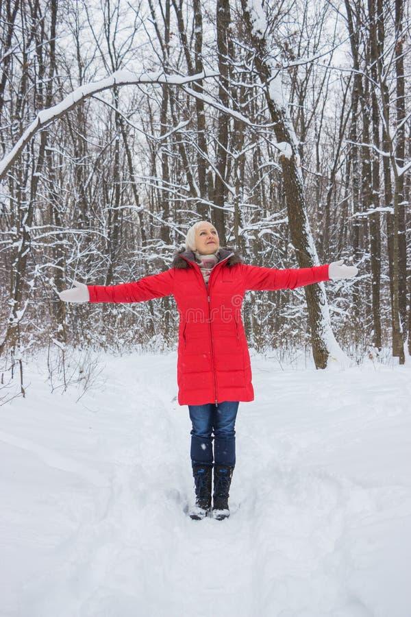 Πορτρέτο μιας συμπαθητικής ανώτερης γυναίκας στο ξύλο χειμερινού χιονιού στο κόκκινο παλτό στοκ φωτογραφίες με δικαίωμα ελεύθερης χρήσης