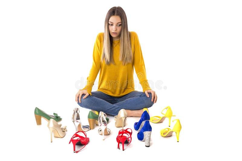 Πορτρέτο μιας συνεδρίασης γυναικών εφήβων στο πάτωμα μεταξύ πολλών ζευγαριών των παπουτσιών ενάντια στο λευκό Έννοια καταναλωτισμ στοκ εικόνα με δικαίωμα ελεύθερης χρήσης