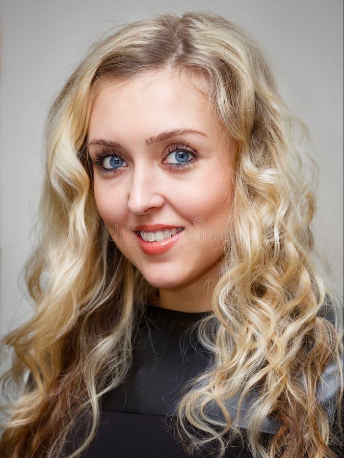 Πορτρέτο μιας χαμογελώντας νέας γοητευτικής γυναίκας με τη μακριά κυματιστή ξανθή τρίχα στοκ εικόνες με δικαίωμα ελεύθερης χρήσης