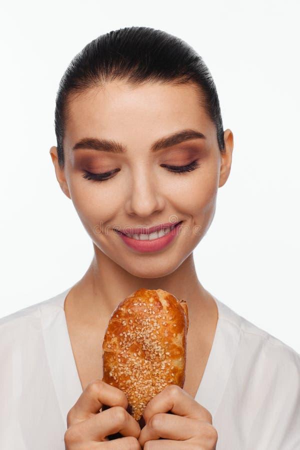 Πορτρέτο μιας χαμογελώντας όμορφης γυναίκας με ένα κουλούρι σουσαμιού στο χέρι της στοκ φωτογραφία με δικαίωμα ελεύθερης χρήσης