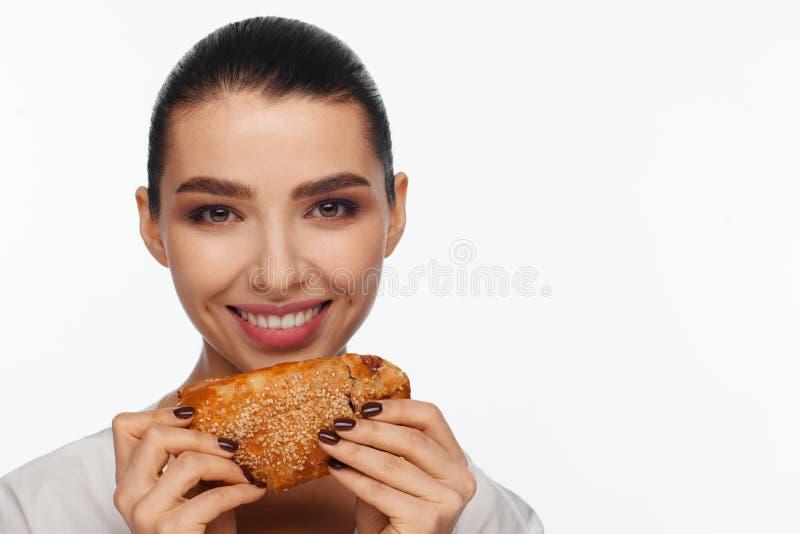 Πορτρέτο μιας χαμογελώντας όμορφης γυναίκας με ένα κουλούρι σουσαμιού στο χέρι της στοκ εικόνα