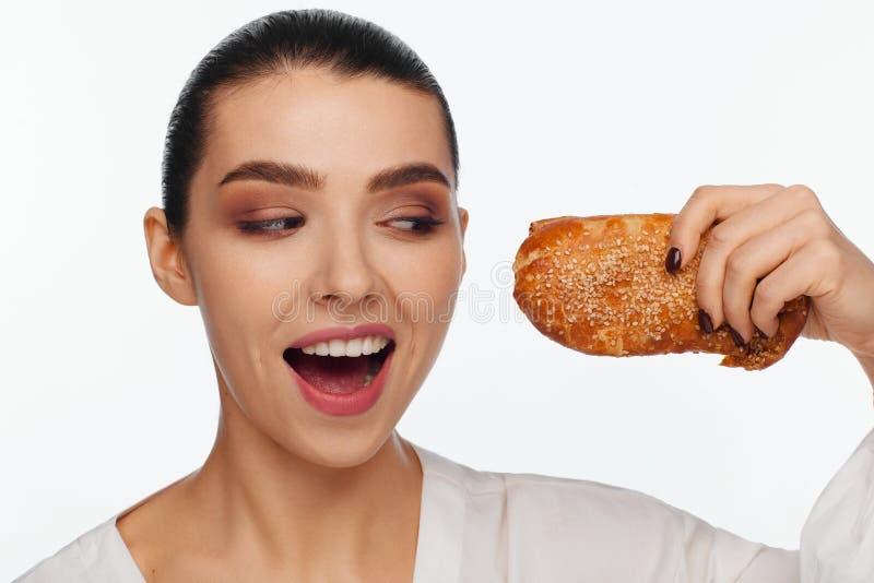 Πορτρέτο μιας χαμογελώντας όμορφης γυναίκας με ένα κουλούρι σουσαμιού στο χέρι της στοκ φωτογραφίες με δικαίωμα ελεύθερης χρήσης