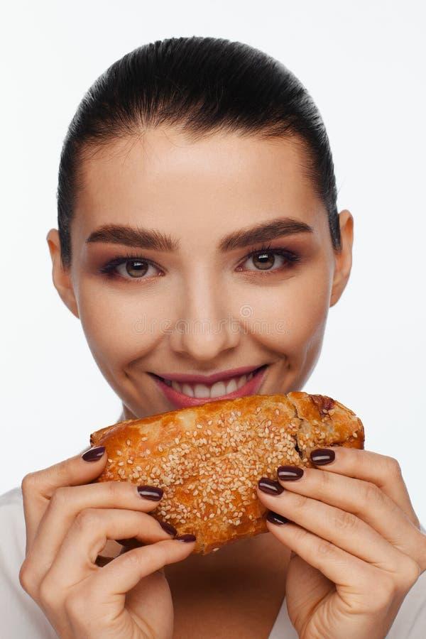 Πορτρέτο μιας χαμογελώντας όμορφης γυναίκας με ένα κουλούρι σουσαμιού στο χέρι της στοκ φωτογραφία