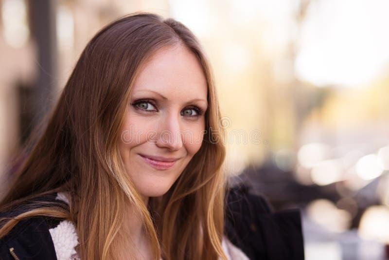 Πορτρέτο μιας χαμογελώντας νέας γυναίκας στην πόλη στοκ εικόνες