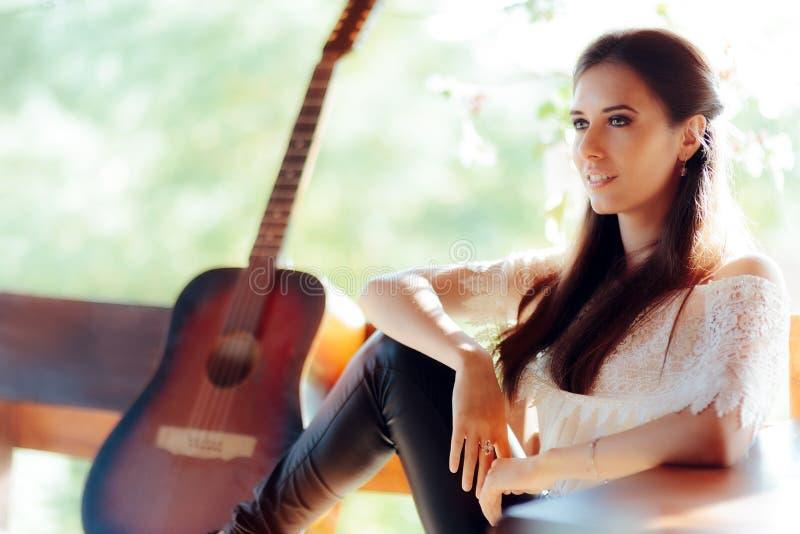 Πορτρέτο μιας όμορφης γυναίκας δίπλα στην κιθάρα της στοκ φωτογραφίες με δικαίωμα ελεύθερης χρήσης