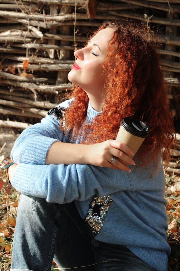 Πορτρέτο μιας όμορφης γυναίκας με την κόκκινη συνεδρίαση τρίχας στη χλόη με τις προσοχές ιδιαίτερες από πίσω από τον ήλιο στοκ φωτογραφία