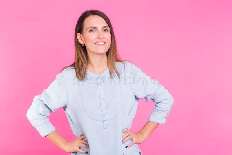 Πορτρέτο μιας όμορφης γυναίκας με τη μακριά καφετιά τρίχα που φορά την μπλε μπλούζα βαμβακιού, που στέκεται τη μέση που χαμογελά  στοκ εικόνα με δικαίωμα ελεύθερης χρήσης