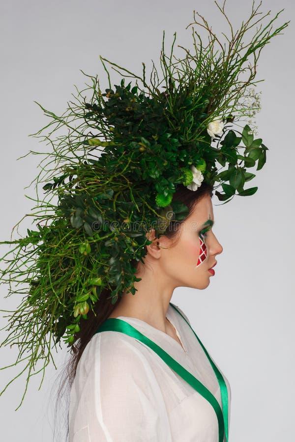 Πορτρέτο μιας όμορφης γυναίκας σε ένα άσπρο φόρεμα με μια πράσινη κορδέλλα και με τους κλάδους στο κεφάλι της Δημιουργικό makeup στοκ φωτογραφία