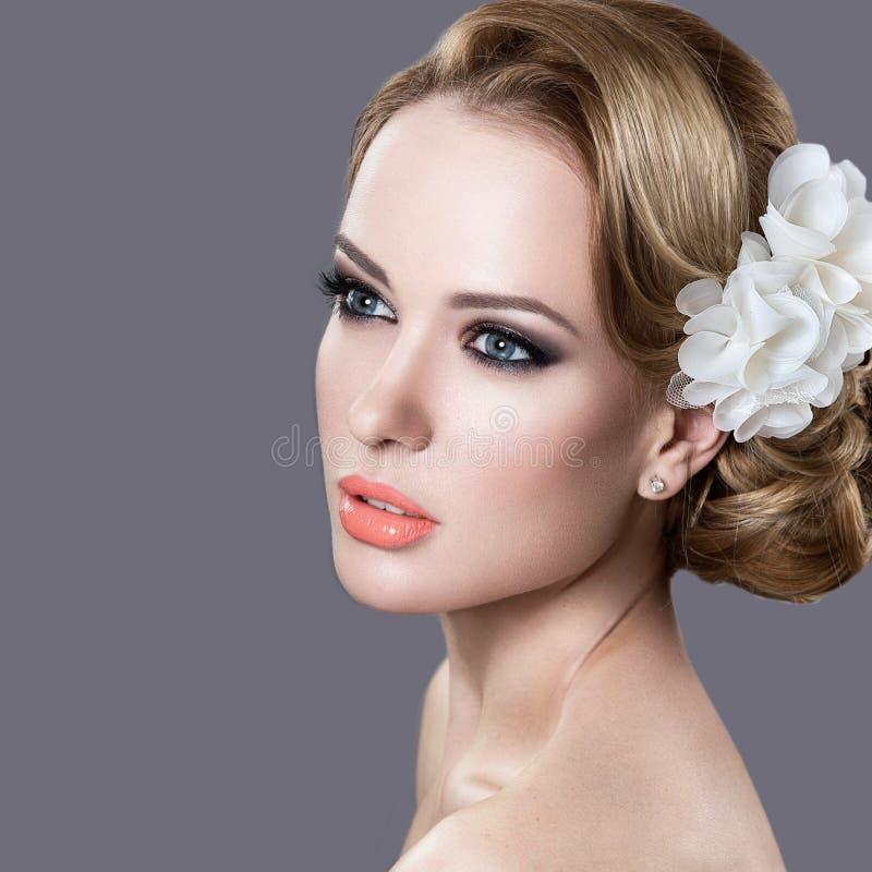 Πορτρέτο μιας όμορφης γυναίκας στην εικόνα της νύφης με τα λουλούδια στην τρίχα της στοκ εικόνα