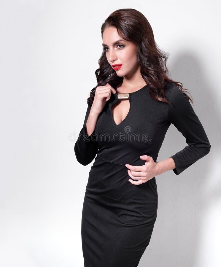 Πορτρέτο μιας όμορφης ενήλικης γυναίκας αισθησιασμού στη μαύρη τοποθέτηση φορεμάτων πέρα από το άσπρο υπόβαθρο Θέα στην πλευρά στοκ φωτογραφίες με δικαίωμα ελεύθερης χρήσης
