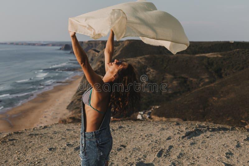 Πορτρέτο μιας όμορφης ευτυχούς νέας γυναίκας που παίζει με ένα χαρτομάνδηλο και τον αέρα στην κορυφή ενός λόφου r lifestyle στοκ εικόνες