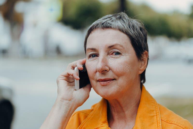 Πορτρέτο μιας όμορφης ηλικιωμένης γυναίκας Ευτυχισμένη γυναίκα στους δρόμους της πόλης με κινητό στοκ εικόνες με δικαίωμα ελεύθερης χρήσης