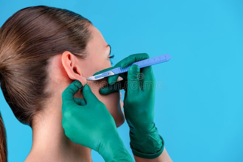 Πορτρέτο μιας όμορφης κινηματογράφησης σε πρώτο πλάνο κοριτσιών, με το ομαλό δέρμα, των χεριών που κρατά ένα χειρουργικό νυστέρι  στοκ εικόνα