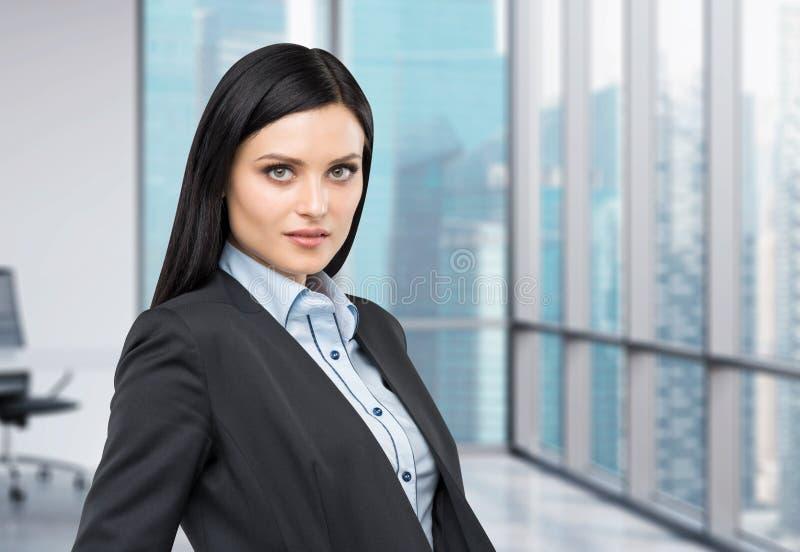 Πορτρέτο μιας όμορφης κυρίας σε ένα επίσημο κοστούμι Πανοραμική άποψη επιχειρησιακών πόλεων από το σύγχρονο γραφείο στοκ εικόνα