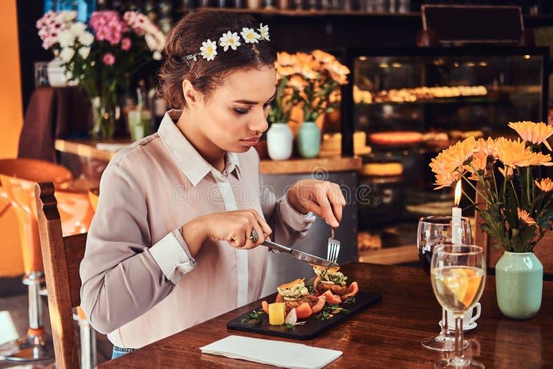 Πορτρέτο μιας όμορφης μαύρος-ξεφλουδισμένης γυναίκας που φορά headband μπλουζών και λουλουδιών, που απολαμβάνει το γεύμα φαγητοσα στοκ εικόνα με δικαίωμα ελεύθερης χρήσης