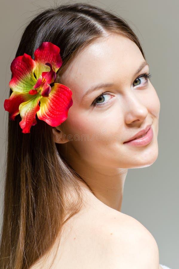 Αγγελικό να φανεί νέο γυναικείο πρόσωπο & κόκκινο orchid λουλούδι στοκ φωτογραφίες