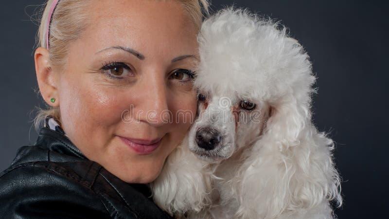 Πορτρέτο μιας όμορφης νέας γυναίκας που αγκαλιάζει το όμορφο σκυλί της στοκ εικόνα με δικαίωμα ελεύθερης χρήσης