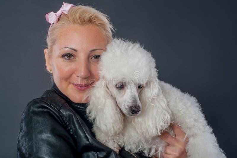 Πορτρέτο μιας όμορφης νέας γυναίκας που αγκαλιάζει το όμορφο σκυλί της στοκ εικόνες