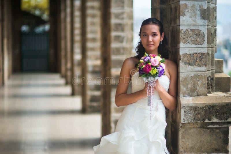 Πορτρέτο μιας όμορφης νύφης σε ένα άσπρο φόρεμα, το οποίο έκλινε σε μια στήλη πετρών στοκ φωτογραφία με δικαίωμα ελεύθερης χρήσης