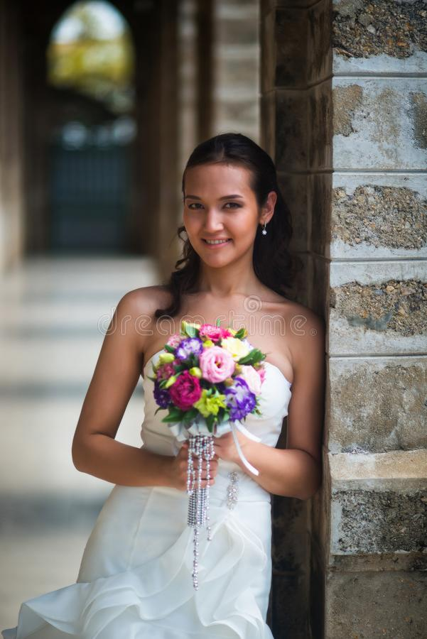 Πορτρέτο μιας όμορφης νύφης στο άσπρο φόρεμα, το οποίο έκλινε σε μια στήλη πετρών στοκ εικόνες με δικαίωμα ελεύθερης χρήσης