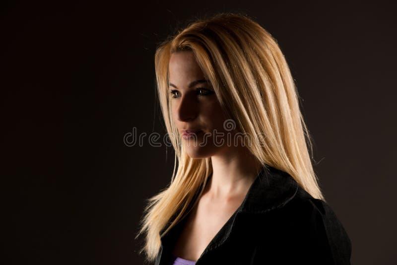 Πορτρέτο μιας όμορφης ξανθής γυναίκας πέρα από το σκούρο γκρι υπόβαθρο στοκ εικόνες με δικαίωμα ελεύθερης χρήσης