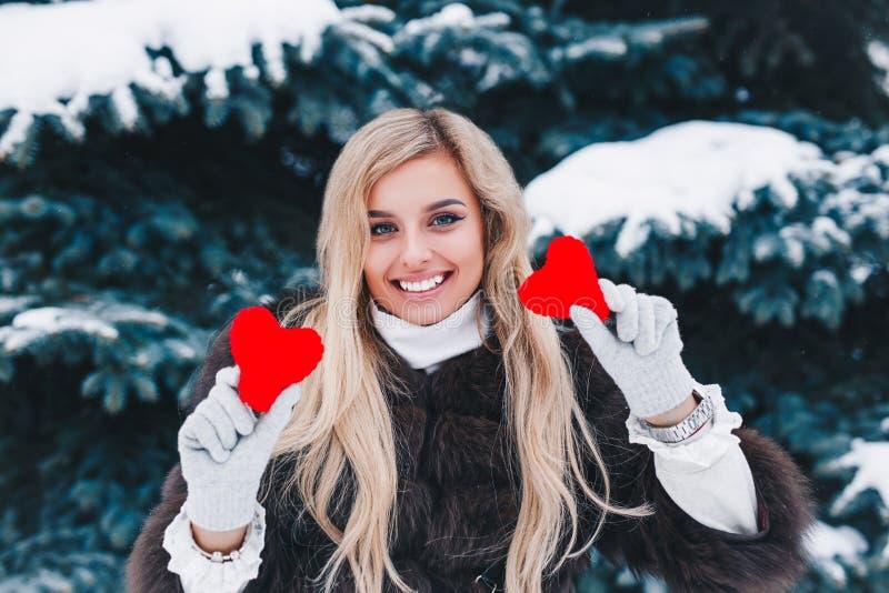 Πορτρέτο μιας όμορφης χαμογελώντας γυναίκας στην καρδιά του δασικού βαλεντίνου εκμετάλλευσης κόκκινου στα χέρια βαλεντίνος ημέρας στοκ εικόνα με δικαίωμα ελεύθερης χρήσης