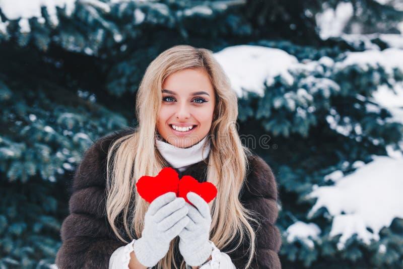 Πορτρέτο μιας όμορφης χαμογελώντας γυναίκας στην καρδιά του δασικού βαλεντίνου εκμετάλλευσης κόκκινου στα χέρια βαλεντίνος ημέρας στοκ φωτογραφίες