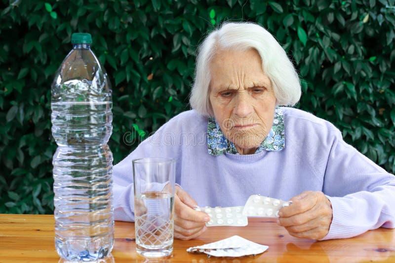 Πορτρέτο μιας όμορφης 90χρονης γυναίκας με χάπια στο χέρι Ηλικιωμένη γυναίκα, με πονοκέφαλο, συναισθηματικό πρόβλημα, άνοια στοκ εικόνες με δικαίωμα ελεύθερης χρήσης