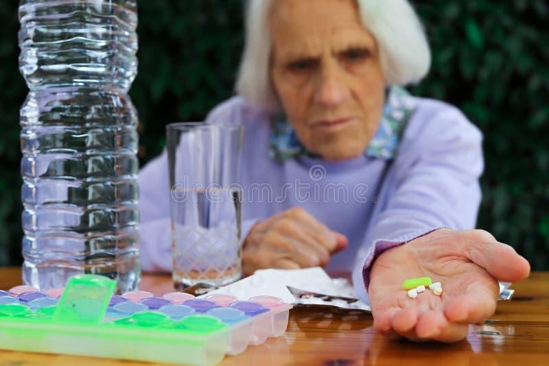 Πορτρέτο μιας όμορφης 90χρονης γυναίκας με χάπια στο χέρι Ηλικιωμένη γυναίκα, με πονοκέφαλο, συναισθηματικό πρόβλημα, άνοια στοκ εικόνα
