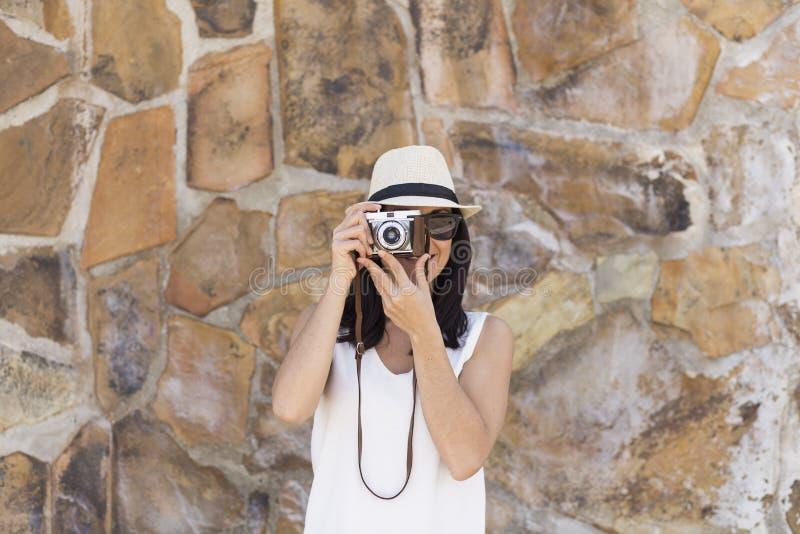 Πορτρέτο μια νέα όμορφη γυναίκα που κρατά μια εκλεκτής ποιότητας κάμερα άνω του s στοκ φωτογραφία