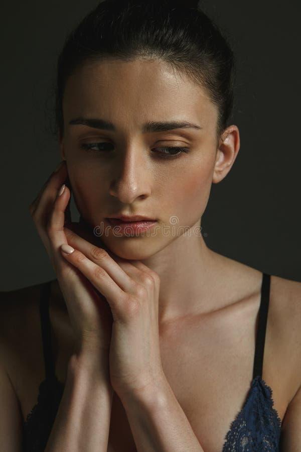 Πορτρέτο μισό-μήκους της νέας λυπημένης γυναίκας στο σκοτεινό υπόβαθρο στούντιο στοκ φωτογραφία με δικαίωμα ελεύθερης χρήσης