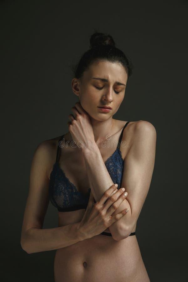 Πορτρέτο μισό-μήκους της νέας λυπημένης γυναίκας στο σκοτεινό υπόβαθρο στούντιο στοκ φωτογραφίες