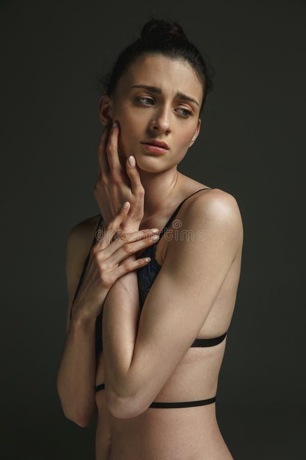 Πορτρέτο μισό-μήκους της νέας λυπημένης γυναίκας στο σκοτεινό υπόβαθρο στούντιο στοκ εικόνες με δικαίωμα ελεύθερης χρήσης