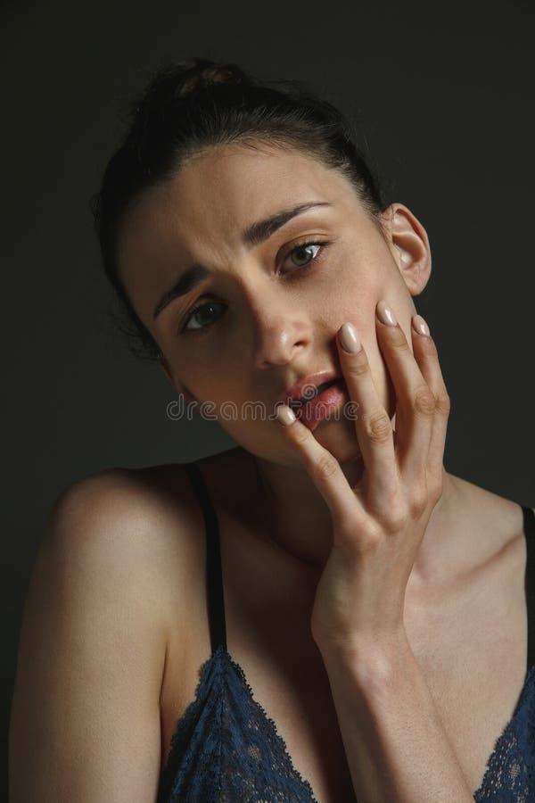 Πορτρέτο μισό-μήκους της νέας λυπημένης γυναίκας στο σκοτεινό υπόβαθρο στούντιο στοκ φωτογραφίες με δικαίωμα ελεύθερης χρήσης