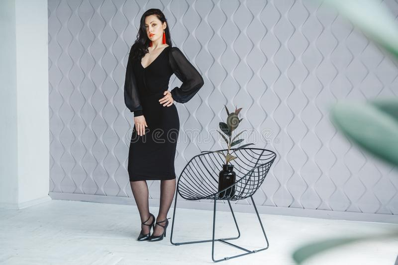 Πορτρέτο μόδας ενός μοντέρνου κοριτσιού brunette που φορά ένα μαύρο φόρεμα Γυναίκα με τα μακρυμάλλη φορώντας κόκκινα σκουλαρίκια  στοκ εικόνες